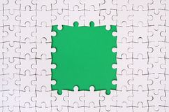 Framing in the form of a rectangle, made of a white jigsaw puzzle around the green space.  Stock Image