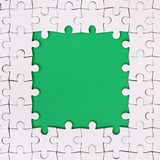 Framing in the form of a rectangle, made of a white jigsaw puzzle around the green space.  Royalty Free Stock Images