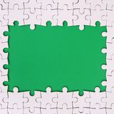Framing in the form of a rectangle, made of a white jigsaw puzzle around the green space.  Royalty Free Stock Photo