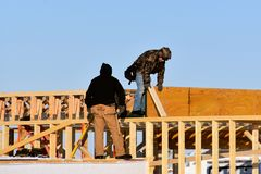 Framing a new house in the winter cold. Construction workers clad in winter clothing work on framing a house in the cold winter stock image