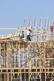 Framing project. New building under construction, carpenters installing frame work Royalty Free Stock Photo