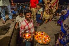Framlägga blommor och stearinljus till heliga Ganges River Arkivfoto