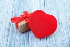 Framlägger ditt älskade, ljusa röda hjärta och gåva som slås in med det röda bandet på ljus träbakgrund Begrepp av dagen för vale royaltyfri bild