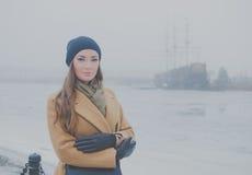 Framme av ett forntida skepp på stranden i vintern går en härlig flicka Arkivfoto