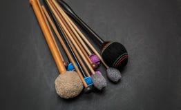 Frammento dei bastoni di legno dettagliati del hickory naturale dell'orchestra di percussione e del tamburo su fondo grigio scuro Fotografia Stock