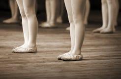 Frammento del banco di balletto con i piedini delle bambine Immagini Stock