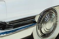 Frammento del cappuccio d'annata bianco dell'automobile con la ruota ed il cuscino ammortizzatore immagine stock