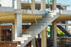 Frammento dell'alloggio residenziale di nuova configurazione sul cantiere, colonne del cemento armato, scala, mucchi dei material Fotografia Stock
