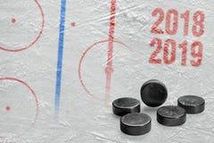 Frammento dell'arena del hockey su ghiaccio con le rondelle immagine stock