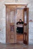 Frammento dell'interno della chiesa del sepolcro santo a Gerusalemme, Israele Il ministro della chiesa sta sedendosi allo scritto Fotografie Stock Libere da Diritti