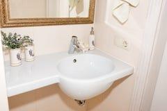 Frammento di un bagno di lusso Bagno bianco moderno esclusivo con il lavandino ed il rubinetto bianchi Immagine Stock