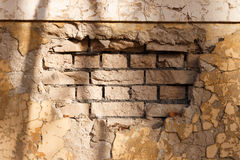 Frammento di un muro di mattoni con gesso crollato Fotografie Stock
