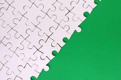 Frammento di un puzzle bianco piegato sui precedenti di una superficie verde della plastica Foto di struttura con lo spazio della immagine stock