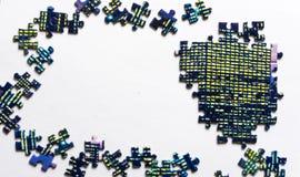 Frammento di un puzzle piegato e un mucchio degli elementi spettinati di puzzle contro i precedenti bianchi Foto con spazio immagini stock