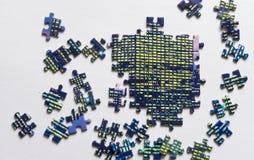 Frammento di un puzzle variopinto piegato e un mucchio degli elementi spettinati di puzzle fotografia stock libera da diritti