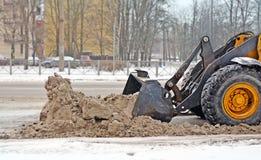Frammento di un trattore che libera la neve dalla carreggiata su una CIT Fotografia Stock Libera da Diritti