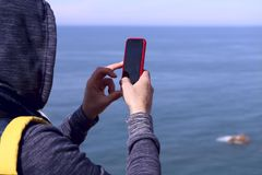 Frammento di un uomo con uno zaino in un rivestimento con un cappuccio sulla sua testa che tiene un telefono in una cassa rossa c fotografia stock