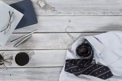 Frammento di una camicia del ` s degli uomini con un legame su un gancio, diario, caffè Fotografia Stock