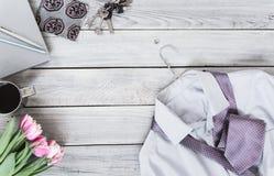 Frammento di una camicia del ` s degli uomini con un legame su un gancio, tulipani, caffè Immagini Stock