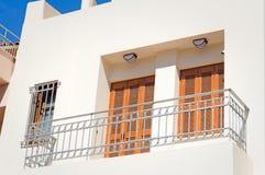 Frammento di una facciata di una casa con un balcone e dei ciechi dalla t immagine stock