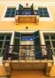 Frammento di una facciata di vecchia casa sulla costa dell'isola di Creta con un balcone e dei ciechi di legno antichi da fotografia stock