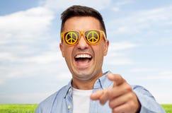 Framsida av att skratta mannen i grön fredsolglasögon arkivbilder
