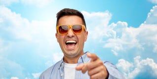 Framsida av att skratta mannen i solglasögon som pekar till dig royaltyfria foton