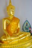 Framsida av den guld- Buddhastatyn och thai konstarkitektur i Wat Bovoranives, Bangkok, Thailand Royaltyfri Bild