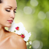 Framsida av den härliga kvinnan med en vit orkidéblomma Royaltyfri Fotografi