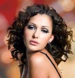 Framsida av den härliga kvinnan med långa lockiga hår Arkivbilder