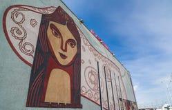 Framsida av den lokala kvinnan med medborgaremodeller på väggen royaltyfri foto