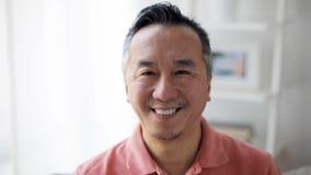 Framsida av den lyckliga le asiatiska mannen hemma lager videofilmer
