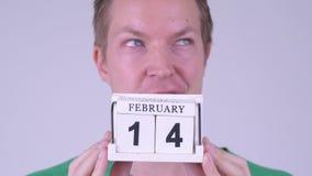Framsida av den lyckliga unga mannen som tänker med kalenderkvarteret som är klart för valentin dag arkivfilmer