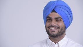 Framsida av den lyckliga unga skäggiga indiska sikh- mannen med att tänka för turban lager videofilmer