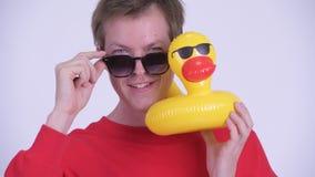 Framsida av den lyckliga unga stiliga mannen med solglasögon som rymmer den uppblåsbara anden stock video