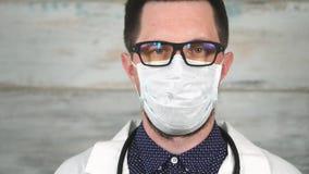 Framsida av den manliga forskaren eller doktorn i den vita skyddande maskeringen lager videofilmer