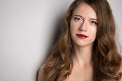Framsida av den unga härliga brunettkvinnan på mörk bakgrund i rött Royaltyfri Fotografi
