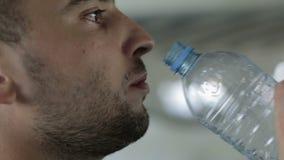 Framsida av det trötta dricksvattnet för ung man lager videofilmer