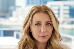 Framsida av en attraktiv blond flicka, blå bakgrund royaltyfri foto