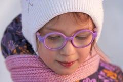 Framsida av en barnflicka i exponeringsglasnärbilden som är upplyst vid aftonvintersolen Flickan ser ner Frostigt soligt för vint Royaltyfri Fotografi