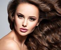 Framsida av en härlig kvinna med långt brunt hår arkivfoto