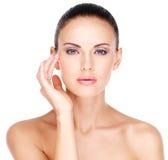 Framsida av en härlig kvinna som rörande hud nära synar Fotografering för Bildbyråer