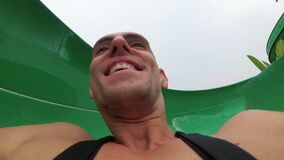 Framsida av en man som stiger ned från extrema vattenglidbanor Första personsikt långsam rörelse lager videofilmer