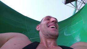Framsida av en man som stiger ned från extrema vattenglidbanor Första personsikt thailand arkivfilmer