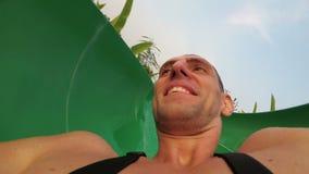 Framsida av en man som stiger ned från extrema vattenglidbanor Första personsikt thailand stock video