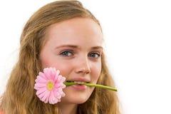 Framsida av flickan med blomman i hennes mun Arkivbild