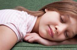 Framsida av lite den söta flickan som sover på en soffa royaltyfri bild