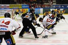 Framsida-avdomare som sätter en puck mellan två ishockeyspelare i ishockeymatch i hockeyallsvenskan mellan SSK och MODO Royaltyfria Bilder
