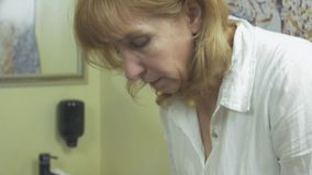 Framsida för framsidacosmetologistwipe av kvinnan i salong vid bomullsblocket efter algmaskering lager videofilmer
