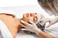 Framsida för kvinna för brunett för plastikkirurgiskönhetbegrepp ung och doktorshand i handske med injektionssprutan royaltyfri foto